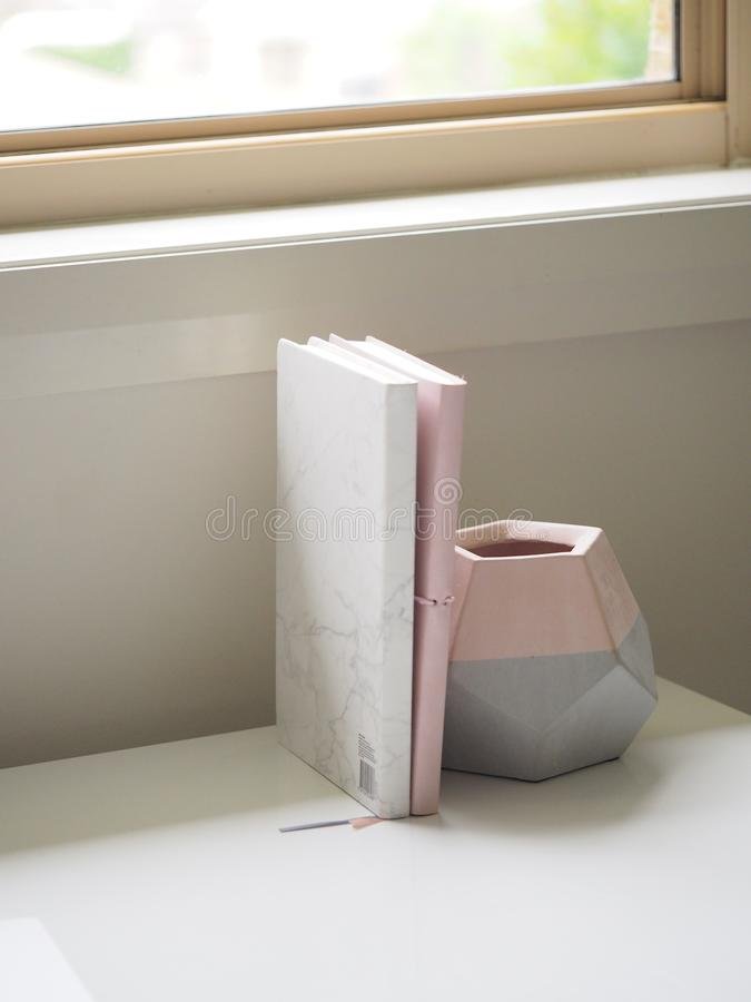 White and Pink Books Piled Beside Pink and Gray Ceramic Vase royalty free stock image