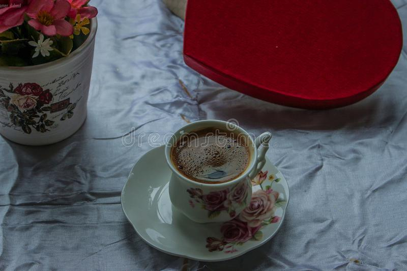 White and Pink Ceramic Teacup Filled With Coffee on White Ceramic Saucer royalty free stock images