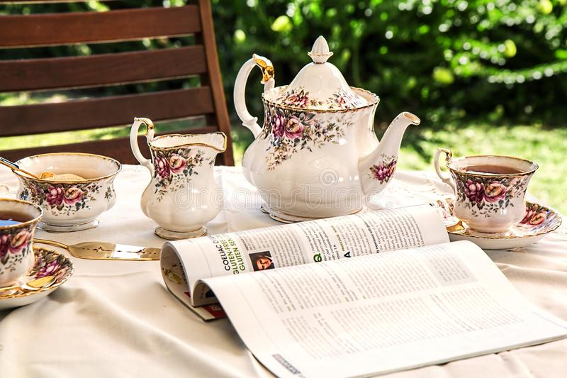 White and Pink Floral Ceramic Tea Set on White Textile Covered Table Beside White and Black Printed Book stock images