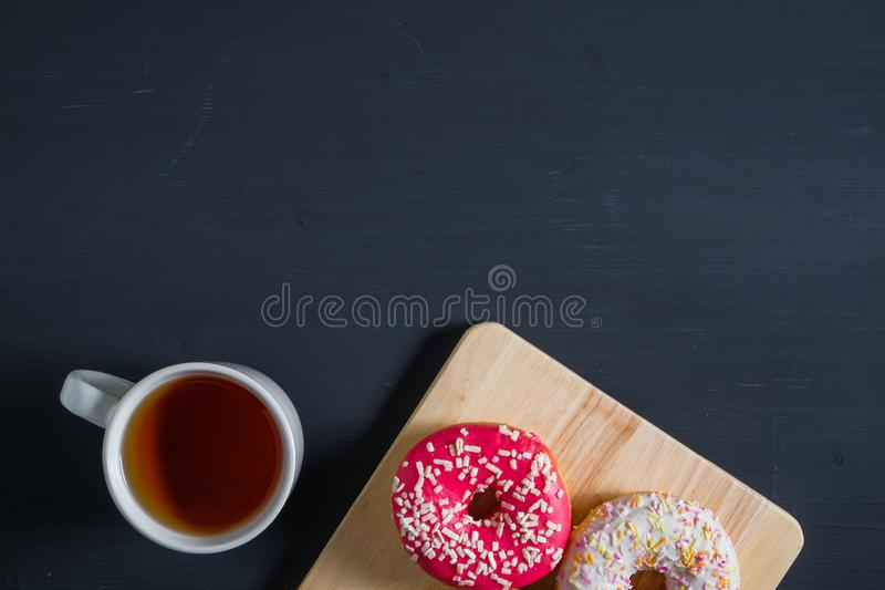 White, pink glazed donuts with cup of tea on black wooden background stock image