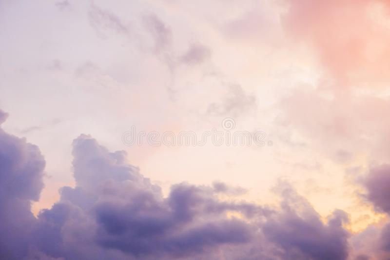 White, pink and gray Cumulus clouds in the free sky during sunset, close-up. Cloudy weather before the rain.  stock photography