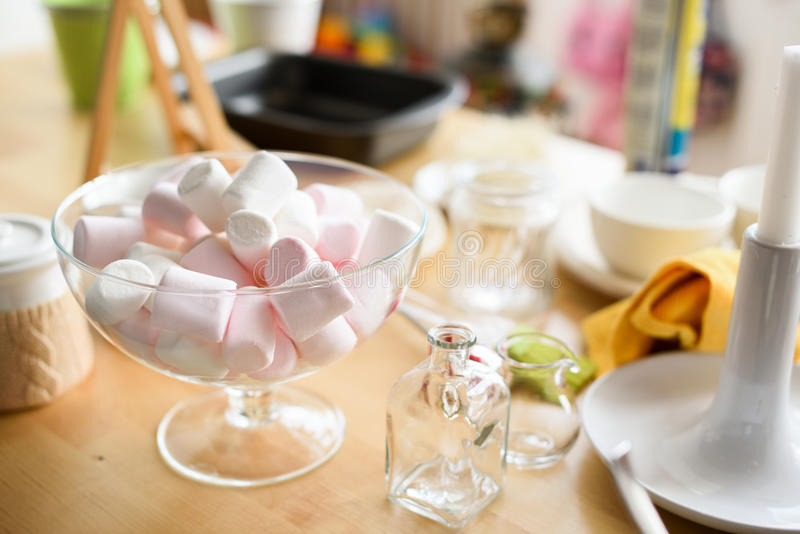 White and pink marshmellows in glass vase and miscellaneous kitchen utensils on dessert table royalty free stock images
