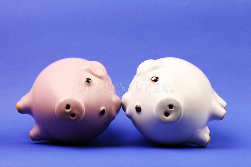 White and pink piggies bank recumbent on blue background royalty free stock image