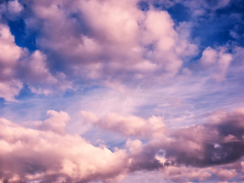 White and pink puffy clouds in blue sky. Create a pattern