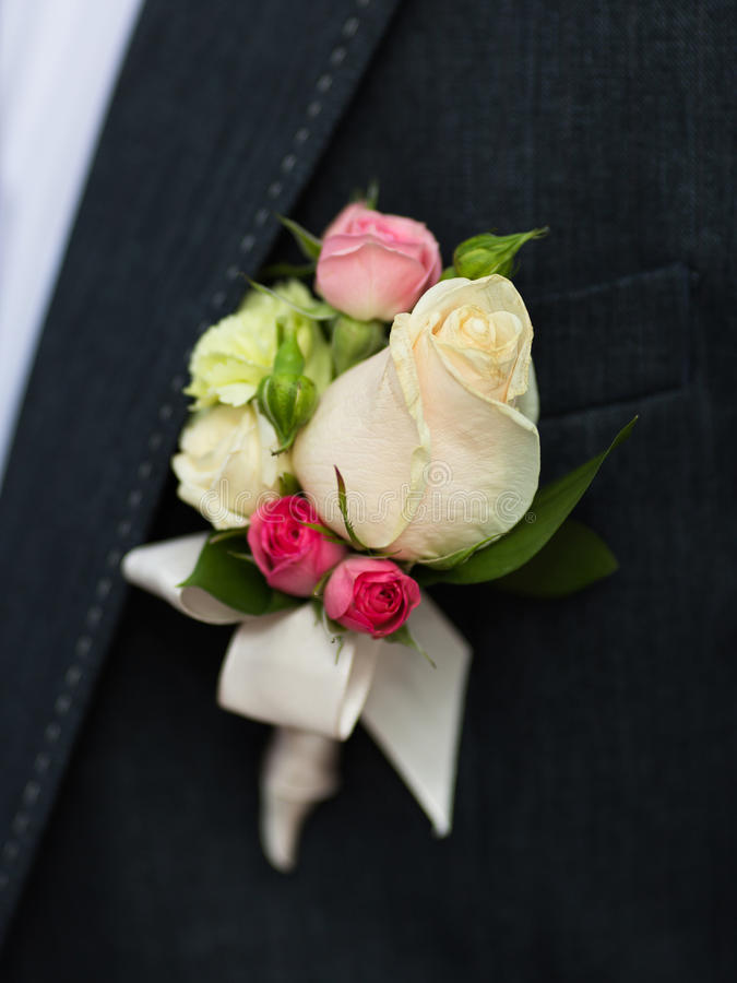 White and pink rose wedding boutonniere on suit royalty free stock photography