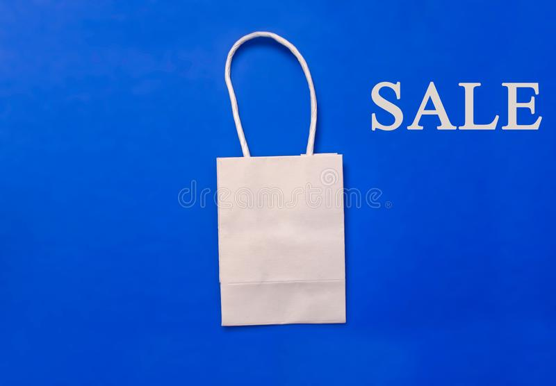 White plain shipping bag on blue background, shopping concept. Copy space stock photography