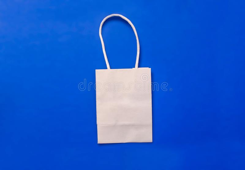 White plain shipping bag on blue background, shopping concept. Copy space stock images