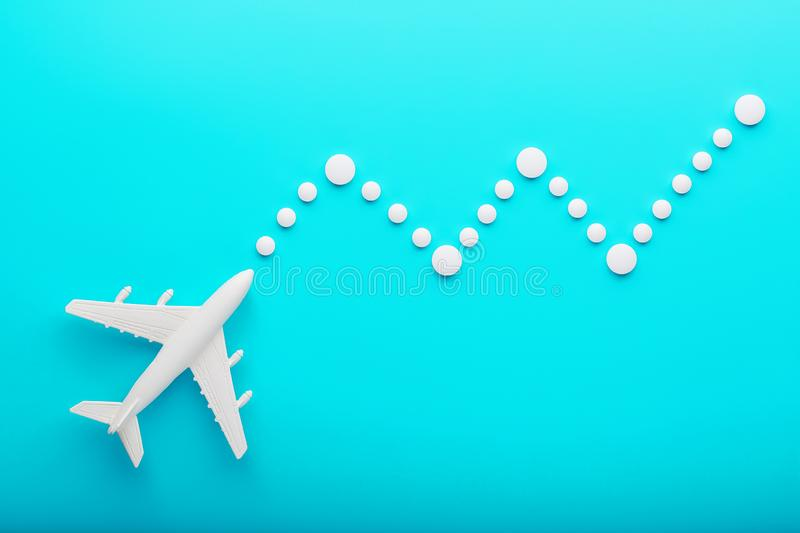 White plane on a blue background with a flexible and smooth trajectory of the route from white points royalty free stock photos