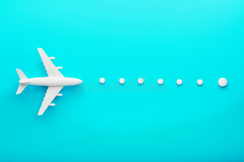 White plane on a blue background with a flexible and smooth trajectory of the route from white points royalty free stock photography