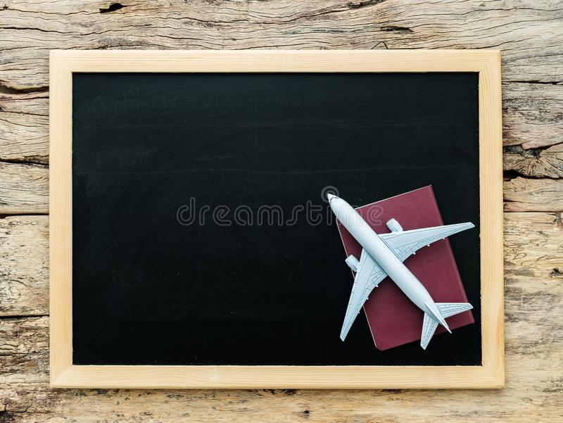 White plane model on red cover passport over blank empty black chalkboard royalty free stock photos