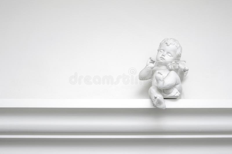 White plaster angel sculpture with a violin royalty free stock image