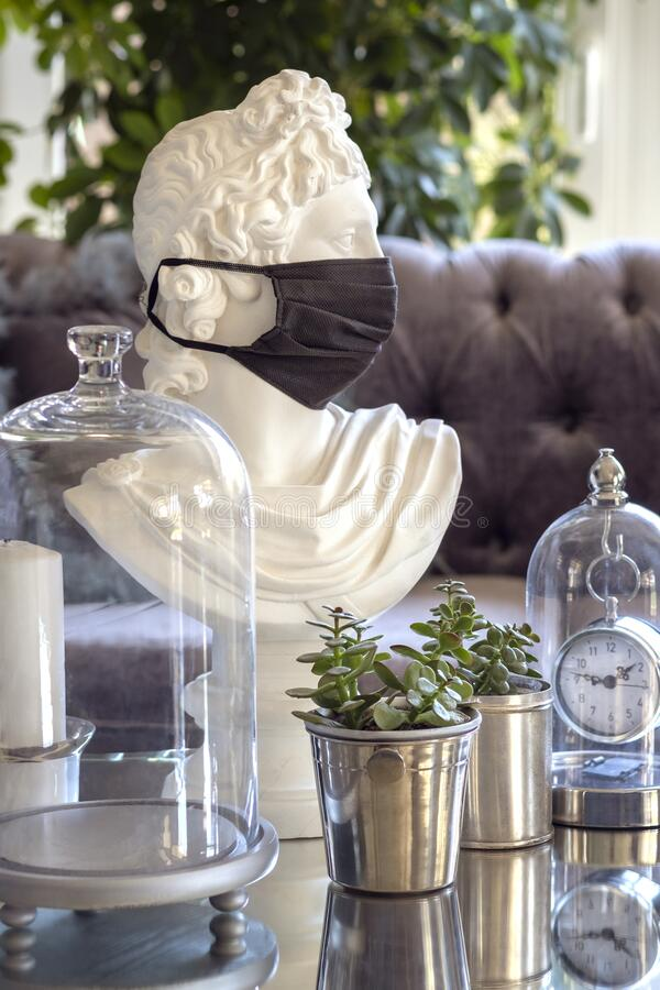 A white plaster statue of bust of Apollo in disposable protective mask covering his face surrounded by glass objects and. A white plaster statue of a bust of stock images