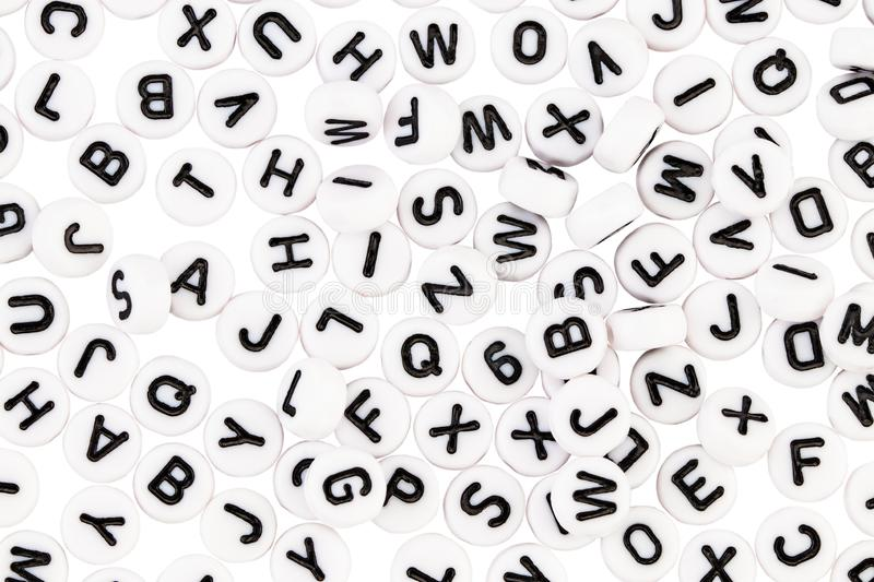 White plastic beads with black letters placed randomly.  stock photography