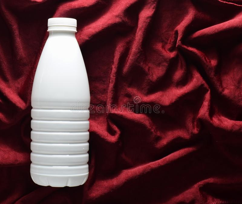 White plastic bottle of yogurt on a red silk tablecloth, top view. White plastic bottle of yogurt on a red silk tablecloth, top view royalty free stock image