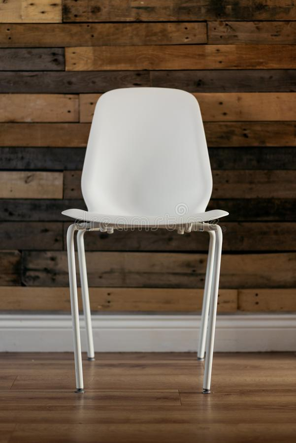 White Plastic Chair Beside Brown Wooden Wall in Home stock images