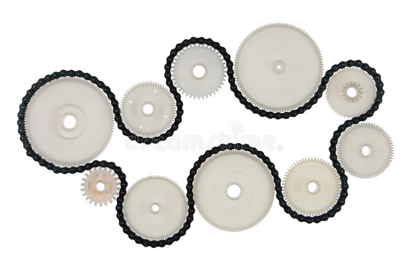 White plastic cogwheels and metal chain, isolated on white background. Transmission concept.  stock photos