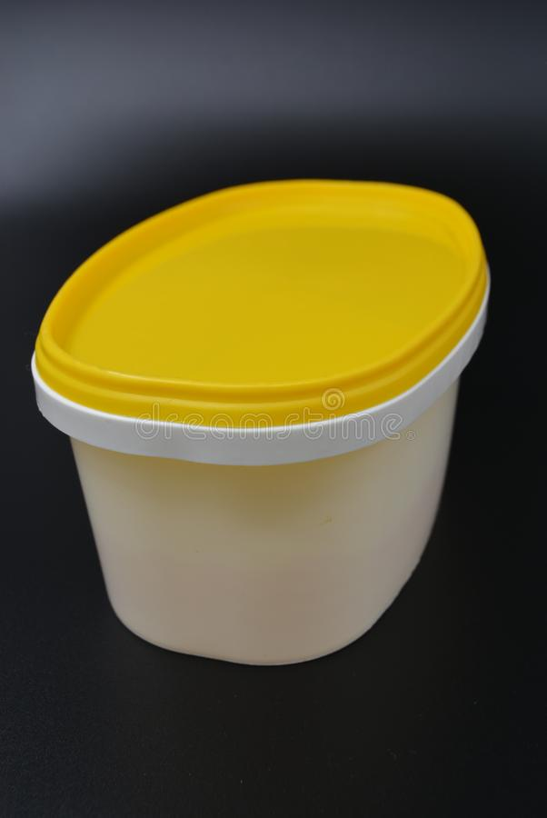 White plastic container for food and mayonnaise with a yellow cap on a black stylish background stock images