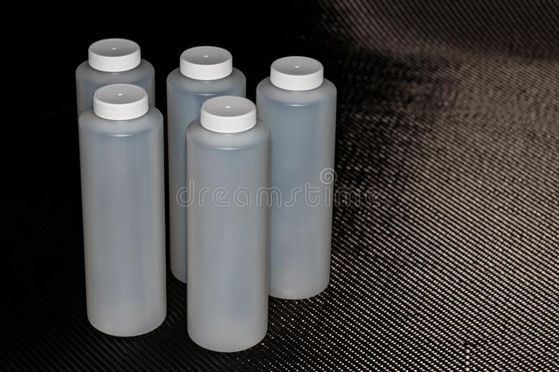White plastic containers with lids on carbon fiber royalty free stock photography