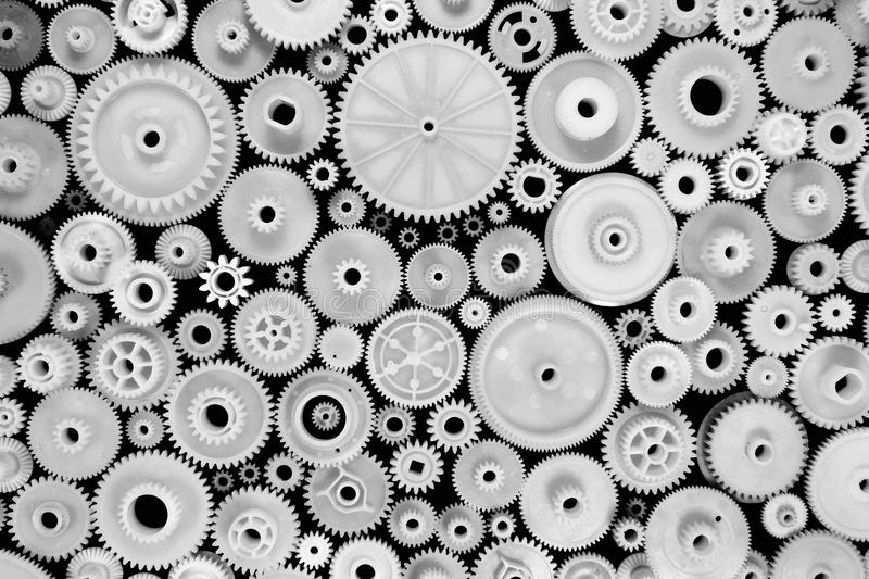 White plastic gears and cogwheels on black background.  stock photo
