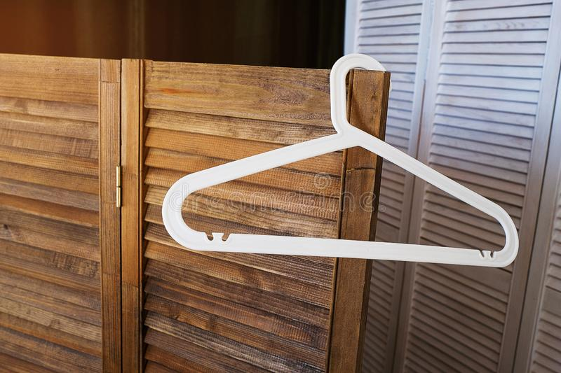 White plastic hanger without clothes, on the background of an empty brown wooden screen and wardrobe stock photo