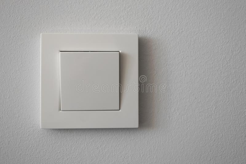 White plastic light switch on light gray wall, close-up. Copy space stock photos