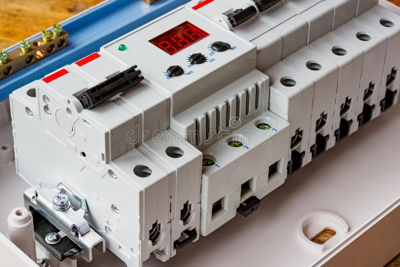 White plastic mounting box with installed automatic circuit breakers and voltage limiter closeup royalty free stock photo