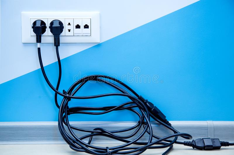 Multiple outlet with a pile of black cable. A white plastic multiple outlet mounted on a light wall with copy space for text, plugs with a twisted pile of black royalty free stock photo