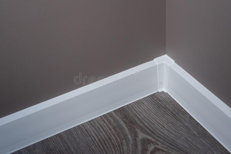 Wall with wallpaper is painted in brown. White plastic plinth. Balcony room after repair. Wallpaper is painted brown royalty free stock image
