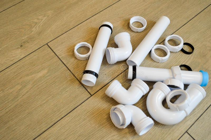White plastic plumbing, plumbing pipes, smooth and curved, fittings, flanges, rubber gaskets. Against the background of beige boards. Place for the inscription stock images