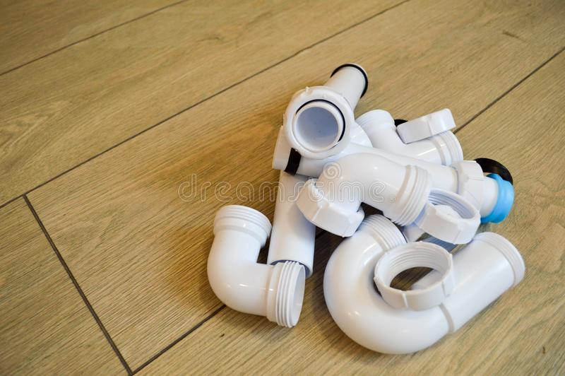 White plastic plumbing, plumbing pipes, smooth and curved, fittings, flanges, rubber gaskets. Against the background of beige boards stock image