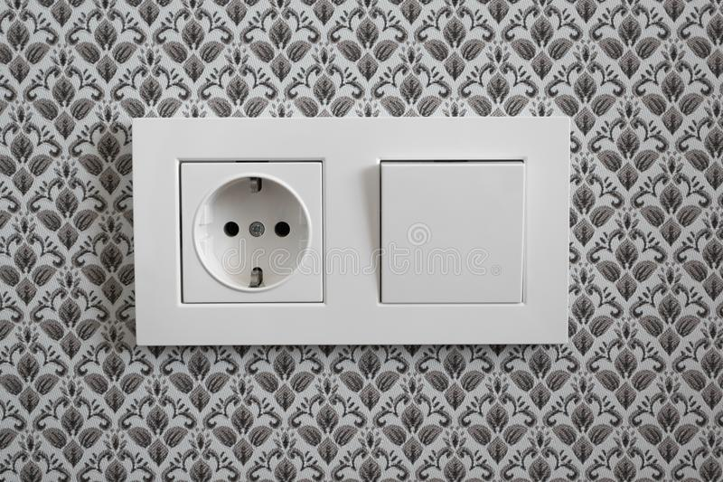 White plastic switched double socket. Light switch and power socket control panel on wall with wallpaper, close-up. Electrical. European equipment stock images