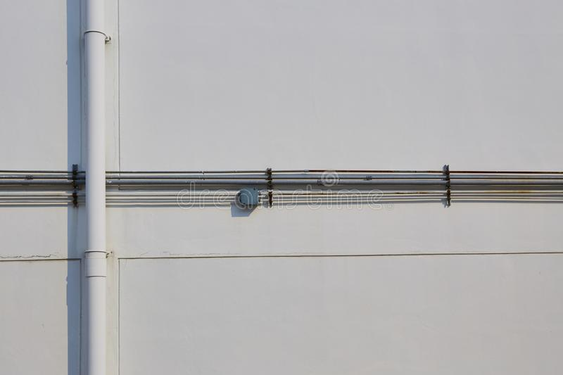 White tube and steel pipe on white wall. White plastic tube and gray steel pipe on white wall stock image