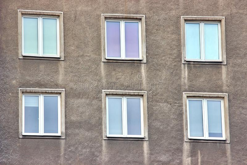 White plastic windows of an apartment building, symmetrical frames in a gray house. many rooms in one house. modern housing. White plastic windows of apartment royalty free stock images
