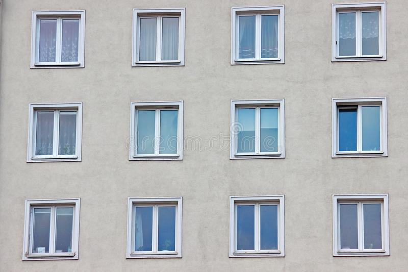 White plastic windows of an apartment building, symmetrical frames in a gray house. many rooms in one house. modern housing. White plastic windows of apartment stock image