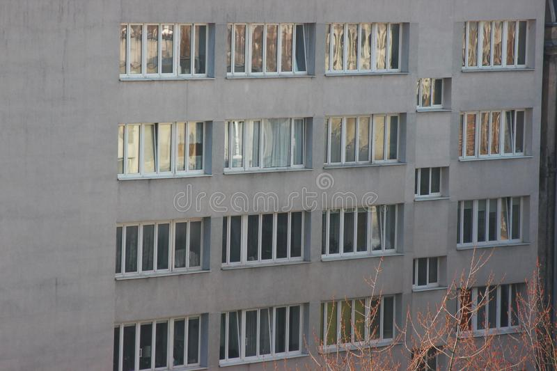 White plastic windows of an apartment building, symmetrical frames in a gray house. many rooms in one house. modern housing. White plastic windows of apartment stock images