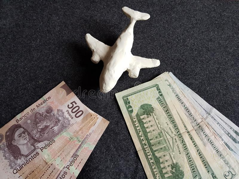White plasticine plane, mexican banknotes and dollar bills on the grey table. Travel and tourism, tax, commerce and exchange, price and offer in flight, cash and stock images