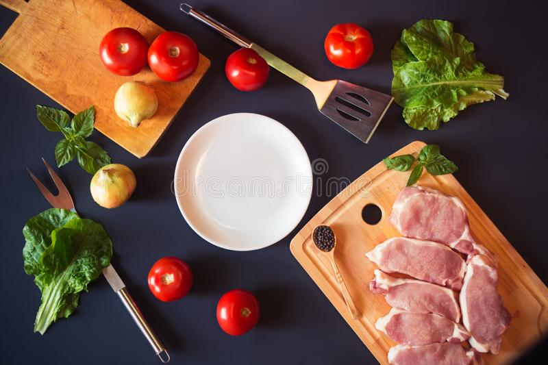 White plate as copy space, fresh raw pork meat and vegetables royalty free stock image