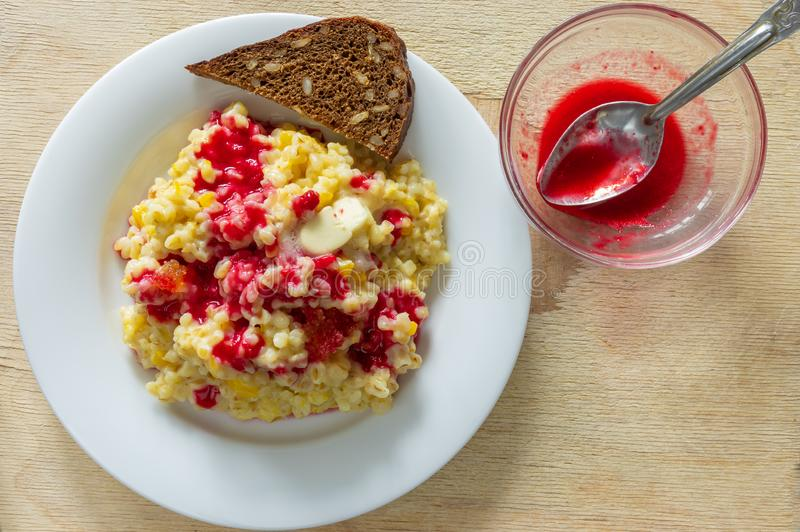 White plate with bulgur cooked in milk with pieces of pumpkin and flavoured with fresh raspberry juice royalty free stock photo