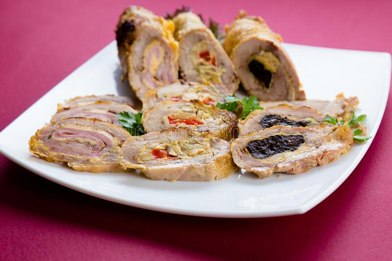 Meat chicken rolls  with vegetable stuffing. White plate with chicken rolls stuffed with carrots, onions and green peas on pink background stock photography