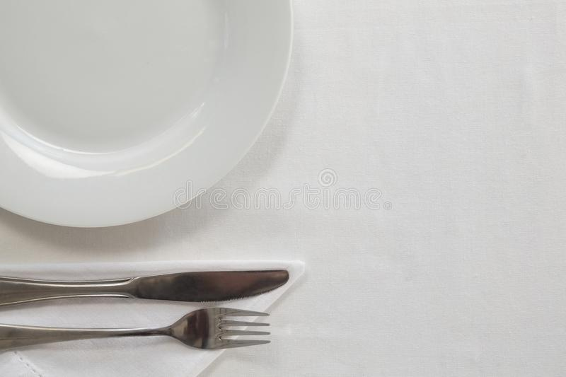 White plate and cutlery set on a table. Close-up of white plate and cutlery set on a table royalty free illustration