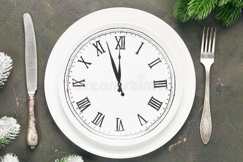 White plate with the dial. And tableware in a frame of their branches of a fir on a dark background. Christmas concept. Top view stock image