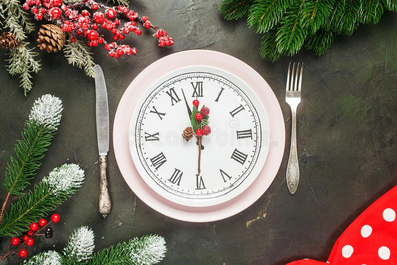 White plate with the dial. And tableware in a frame of their branches of a fir on a dark background. Christmas concept. Top view stock photos