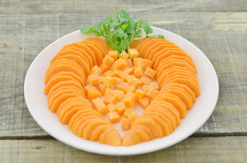 White plate with diced and slices carrots on wooden table, closeup stock images