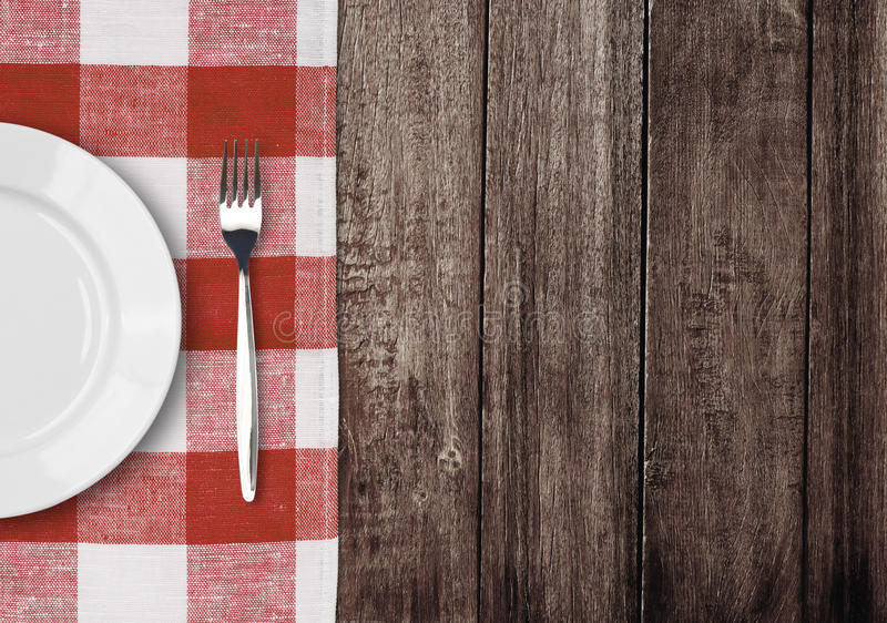 White plate and fork on old wooden table. With red checked tablecloth and copyspace