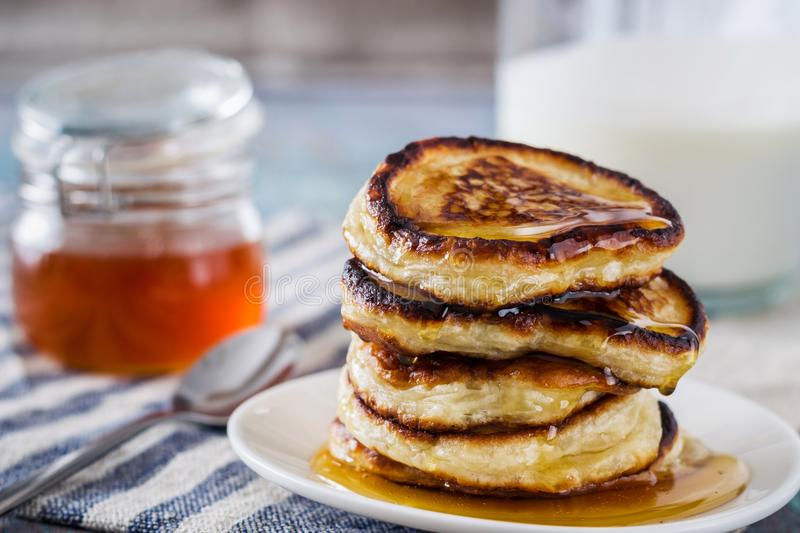 White plate full of pancakes on a wooden background. And honey stock image