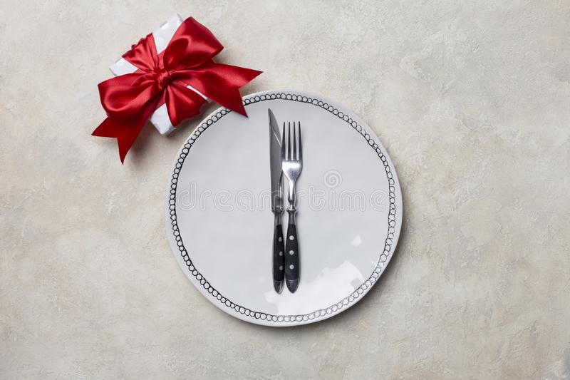 White plate with gift box near, with fork and knife at white background for celebration Valentine`s day royalty free stock image