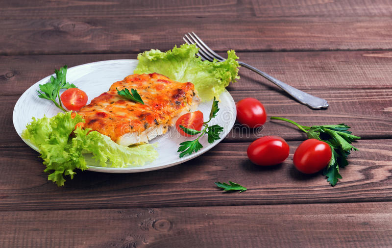 white plate glass portion of the baked cod fish royalty free stock image