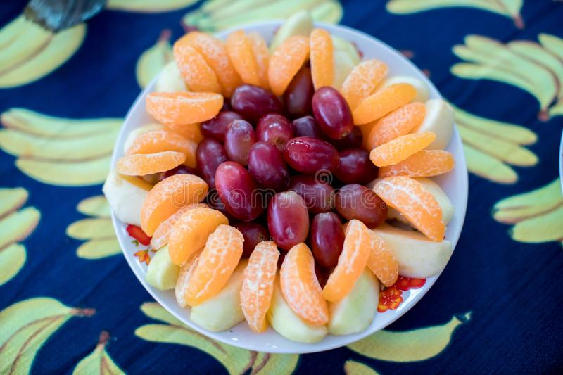 White plate, with grapes and orange Healthy and beauty fruits concept. art food decoration. royalty free stock photography