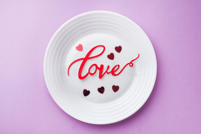 White plate inscription love on a pink background. Concept Valentine`s day royalty free stock photo