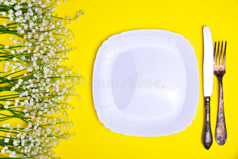 White plate and iron cutlery on a yellow background royalty free stock image